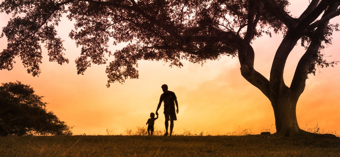 Father walking with is son at the park at sunset